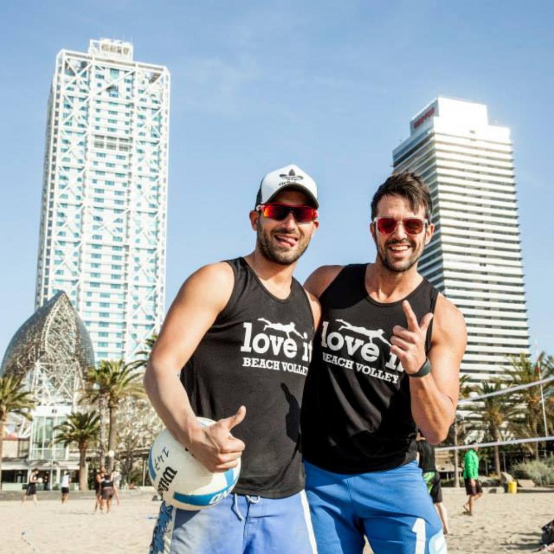 """alt= """"Dos jugadores de voley playa saludando a la cámara"""""""