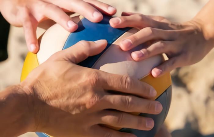"alt= ""Personas tocando un balón de voley playa"""